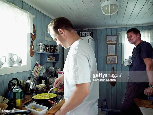 Two men preparing food in kitchen