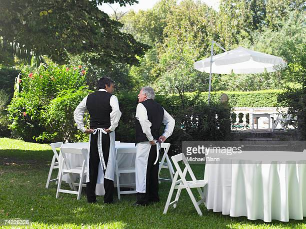 'Two men preparing garden party, rear view'