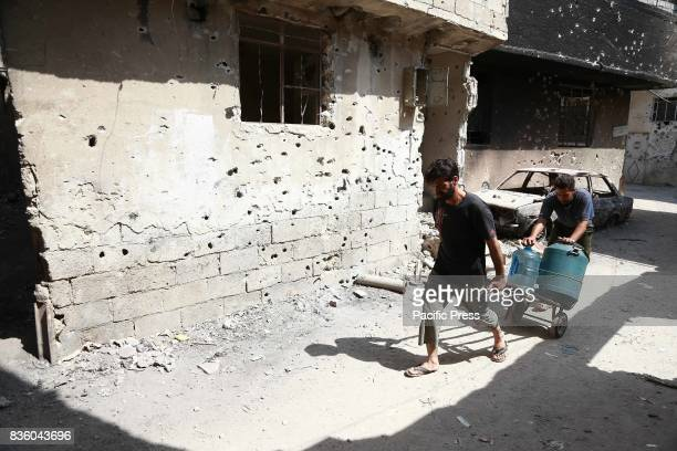 Two men pull a cart containing water on a damaged road in Zamalka in the eastern Ghouta and this area is under the control of the Syrian opposition