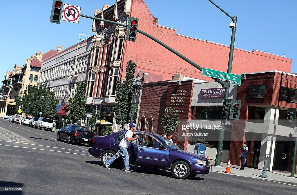 Two men push a car after it stalled on June 27, 2012 in Stockton, California. Members of the Stockton city council voted 6-1 on Tuesday to adopt a spending plan for operating under Chapter 9 bankruptcy protection following failed talks with bondholders and labor unions failed. The move will make Stockton the biggest U.S. city to file for bankruptcy protection from creditors.