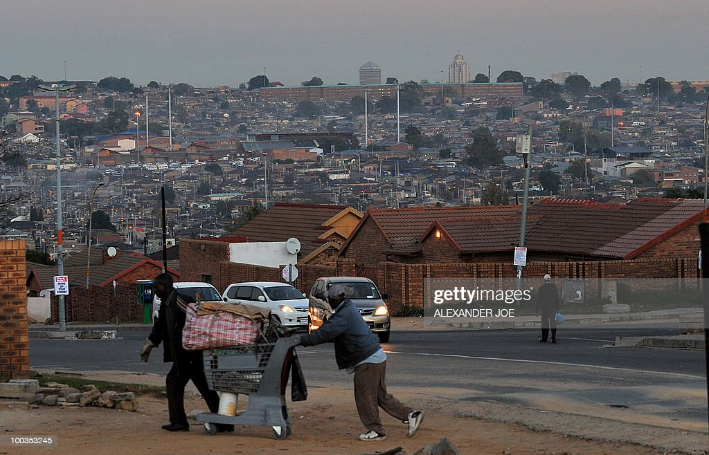 Two men push a trolley in the township of Alexandra in the north of Johannesburg in the rich suburb of Sandton on May 23 2010 AFP PHOTO / ALEXANDER...