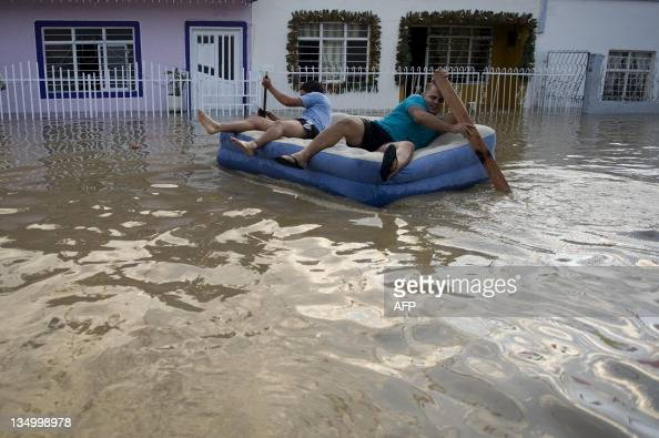 Two men put a mattress to use a flooded street after the Cauca River overflowed on December 5 in Cali Valle del Cauca department Colombia At least 96...