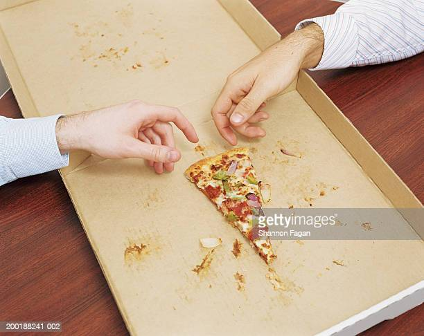 Two men reaching for last slice of pizza, elevated view, close-up