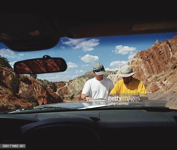Two men reading map on bonnet of car, view through front window