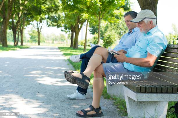 Two men reading while sitting on bench on The Trail of Remembrance and Comradeship in Ljubljana, Slovenia