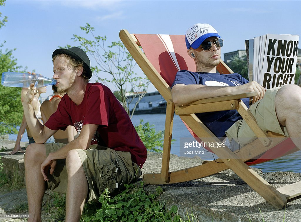 Two men relaxing in deckchair, drinking bottled water : Stock Photo