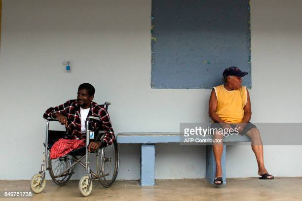 Two men rest at a shelter as Hurricane Maria approaches Puerto Rico in Fajardo on September 19 2017 Maria headed towards the Virgin Islands and...