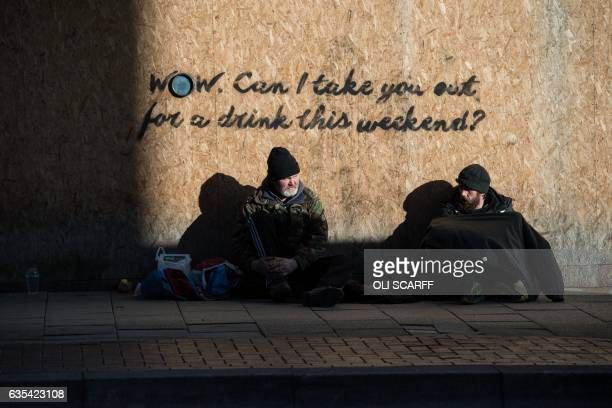 TOPSHOT Two men rest on the pavement in front of a boardedup shop in the centre of StokeonTrent central England on February 13 2017 The byelection...