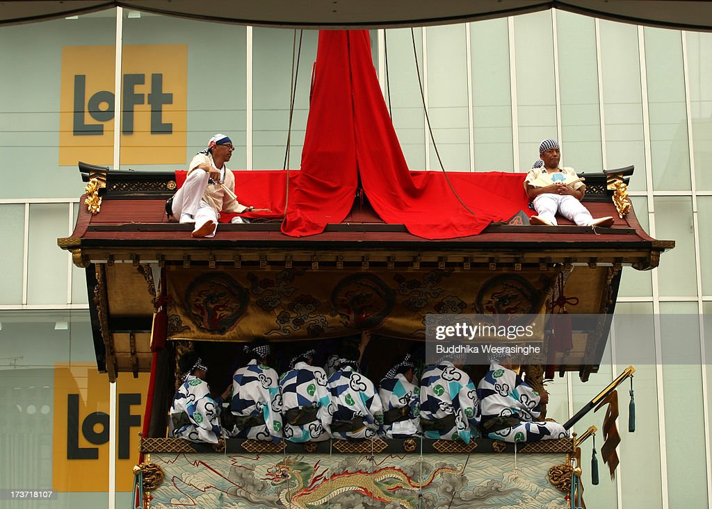 Two men rest on the roof of float named Yamahoko during the annual Kyoto Gion Festival parade on July 17, 2013 in Kyoto, Japan. The Gion festival is one of three biggest Japanese festivals. dating back to the 9th century, the festival is part of a ritual intended to satisfy the Gods that brought on fire, floods and earthquakes. During the festival the streets are decorated with lanterns and many of the women dress in 'yukata', summer kimonos.