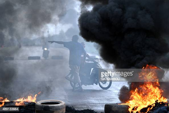 Two men ride a motorbike close to a barrier of burning tires on September 19 2015 in Ouagadougou Burkina Faso's capital The protest comes several...