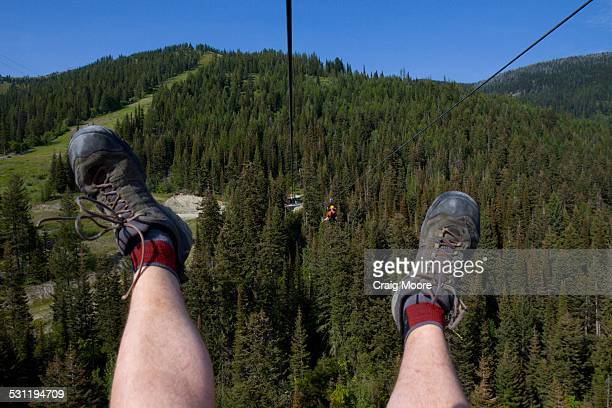 Two men ride a zip line at Whitefish, Montana.