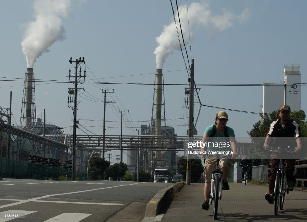 Two men ride bicycle beside the commercial industrial scene on May 18, 2013 in Osaka, Japan. Japan's economy recently shows the sign of recovery as the growth of last quarter was 0.9 percent, or 3.5 percent on annual basis.