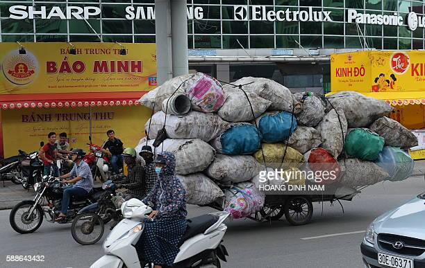 Two men ride on a motorcycle pulling a cart with a big load of recyclable items on a Hanoi street on August 12 2016 Vietnam's economy slowed in the...