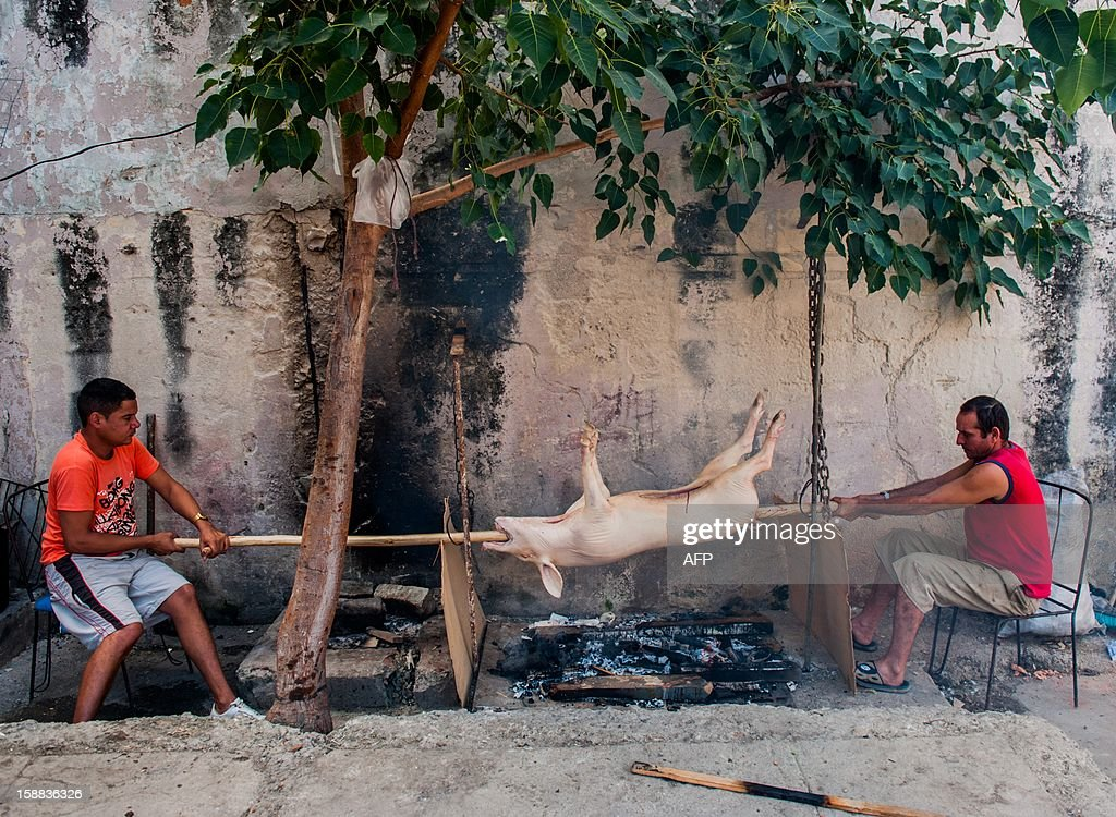 Two men roast a pig for New Year´s Eve celebrations in Havana on December 31, 2012.