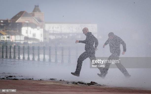 Two men run from a wave whipped up by Hurricane Ophelia as it crashes over the seafront in Penzance on October 16 2017 in Cornwall England Hurricane...