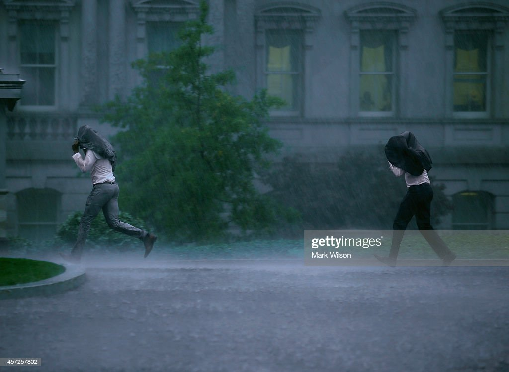 Two men run through the rain at the White House as a storm approaches on October 15 2014 in Washington DC The Washington area was issued a tornado...