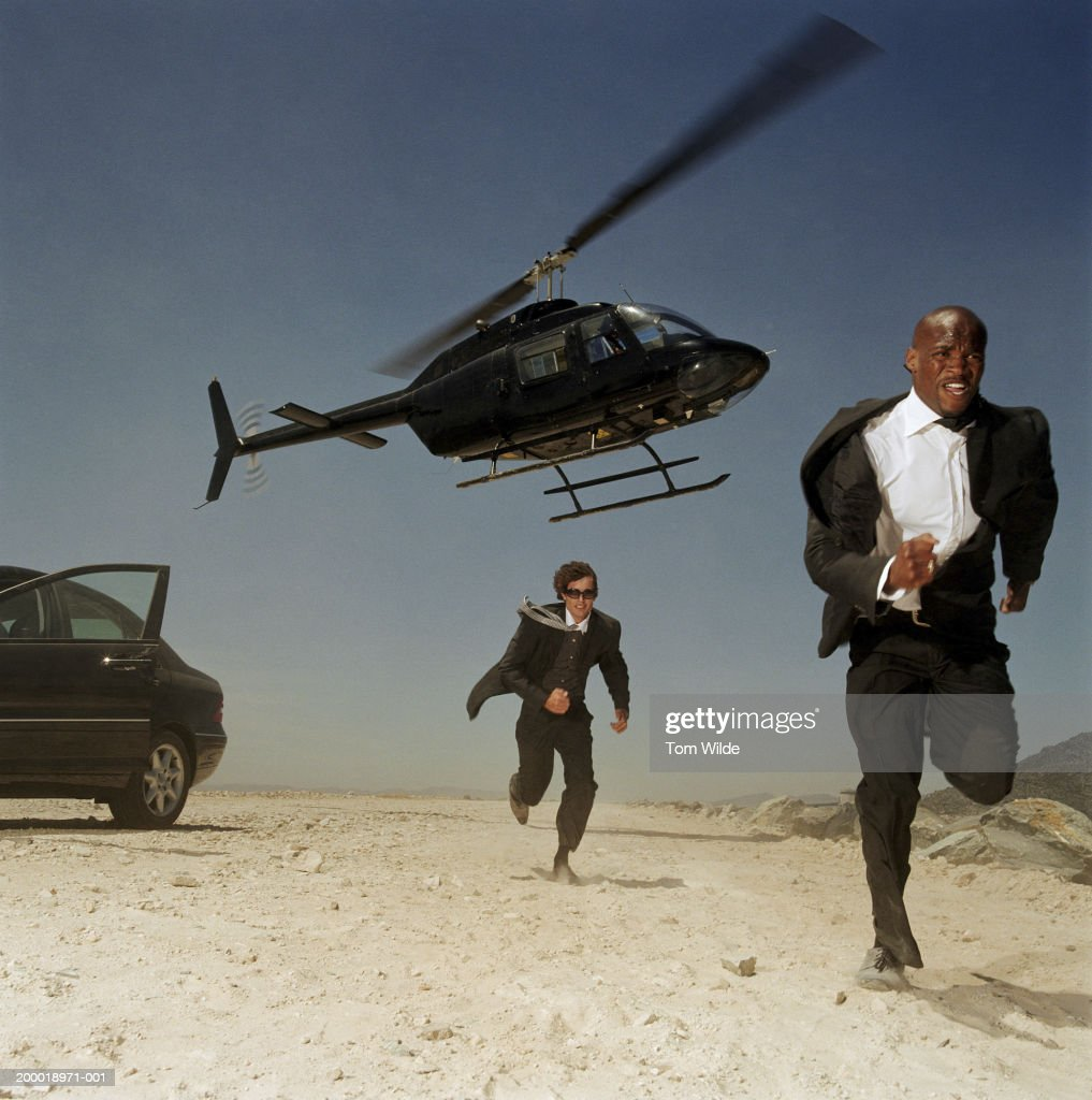 Two men running from helicopter in desert
