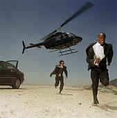 Two men running from helicopter in desert