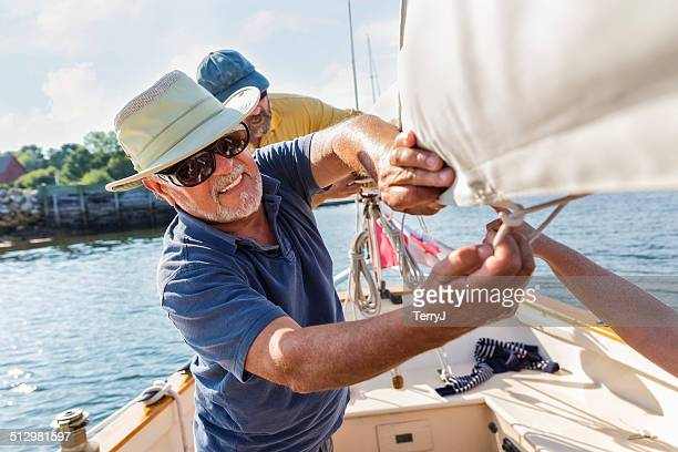 Two Men Secure the Sail on a Sailboat
