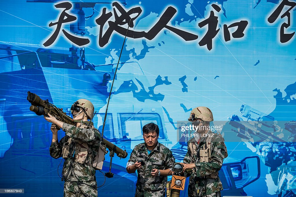 Two men set up a weapon model next to a mannequin at a display of Chinese manufacturer Tianhe Defence during the 9th China International Aviation and Aerospace Exhibition in Zhuhai on November 13, 2012. China's air show comes as the Communist Party holds a meeting to select the country's new leaders -- including the party's Central Military Commission, which controls the armed forces. AFP PHOTO / Philippe Lopez