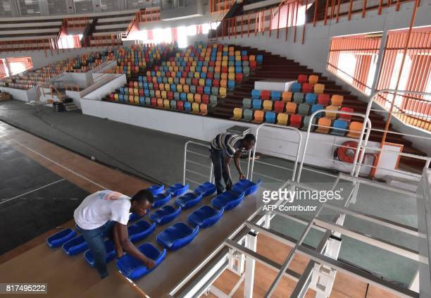 Two men set up seats in the basketball arena on July 17 2017 at the Treichville sports hall in Abidjan ahead of the Jeux de la Francophonie PHOTO /...