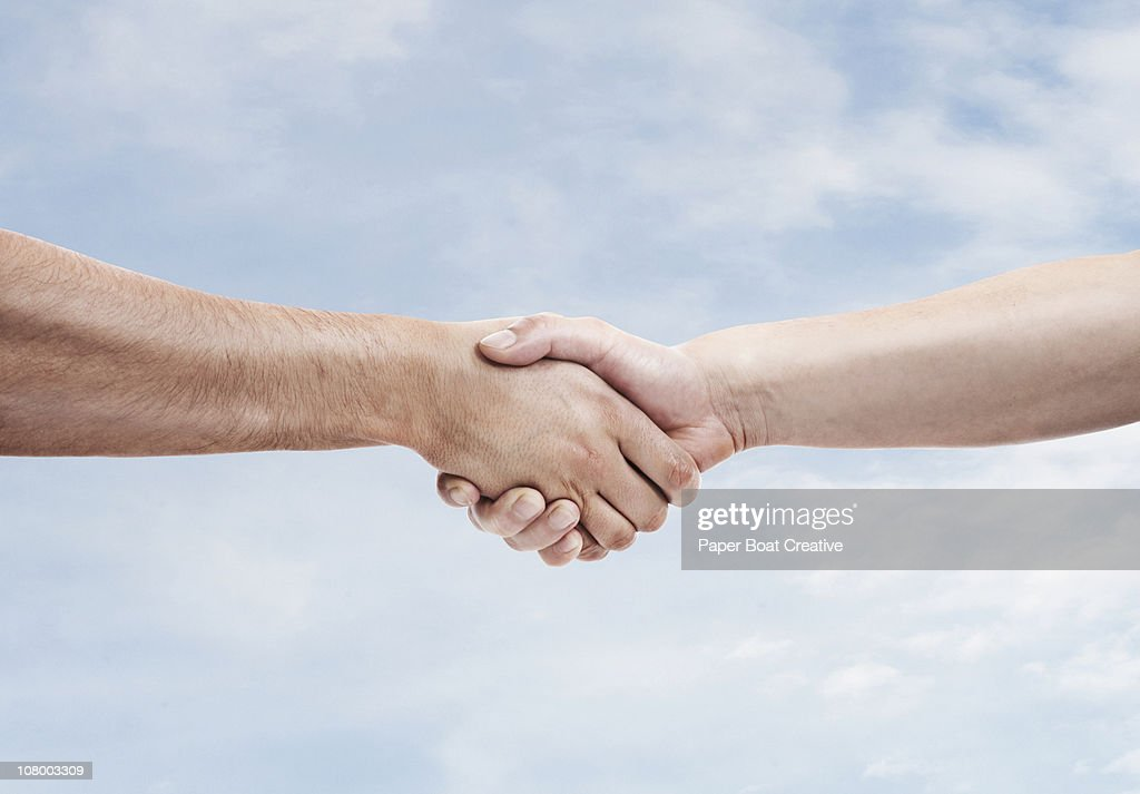 Two men shaking hands againt sky background : Stock Photo