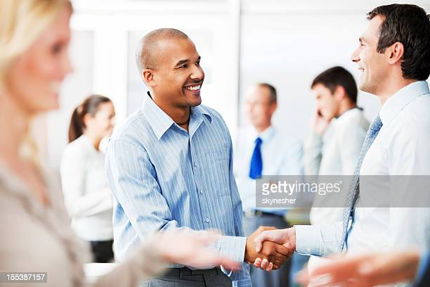 Two men shaking hands in business surroundings