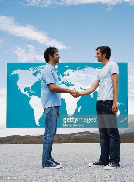 Deux hommes se serrant la main à l'avant de la carte du monde en plein air