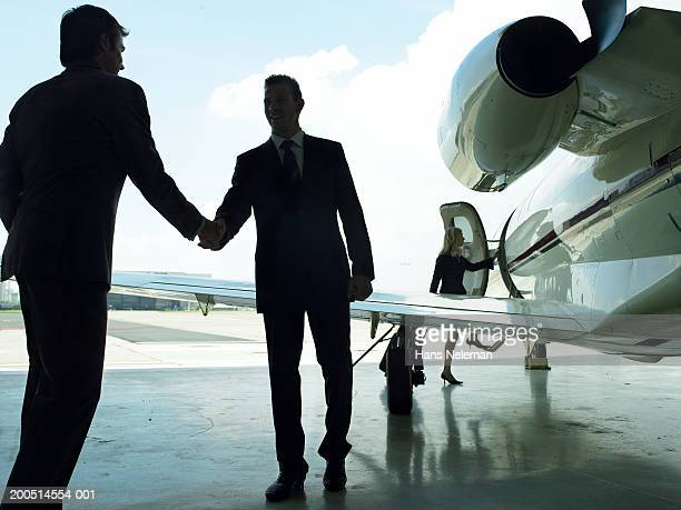 Two men shaking hands outside of private plane, low angle view