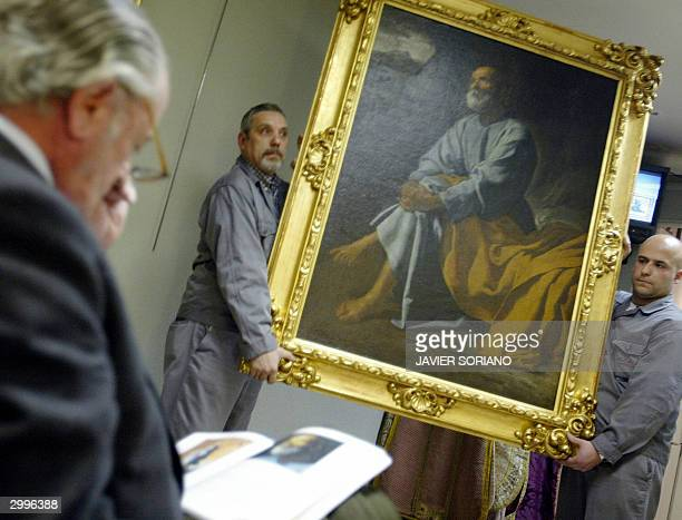 Two men show a painting of Spanish artist Diego Velazquez 'The Tears of San Pedro' to possible buyers during an auction in Madrid 19 February 2004...