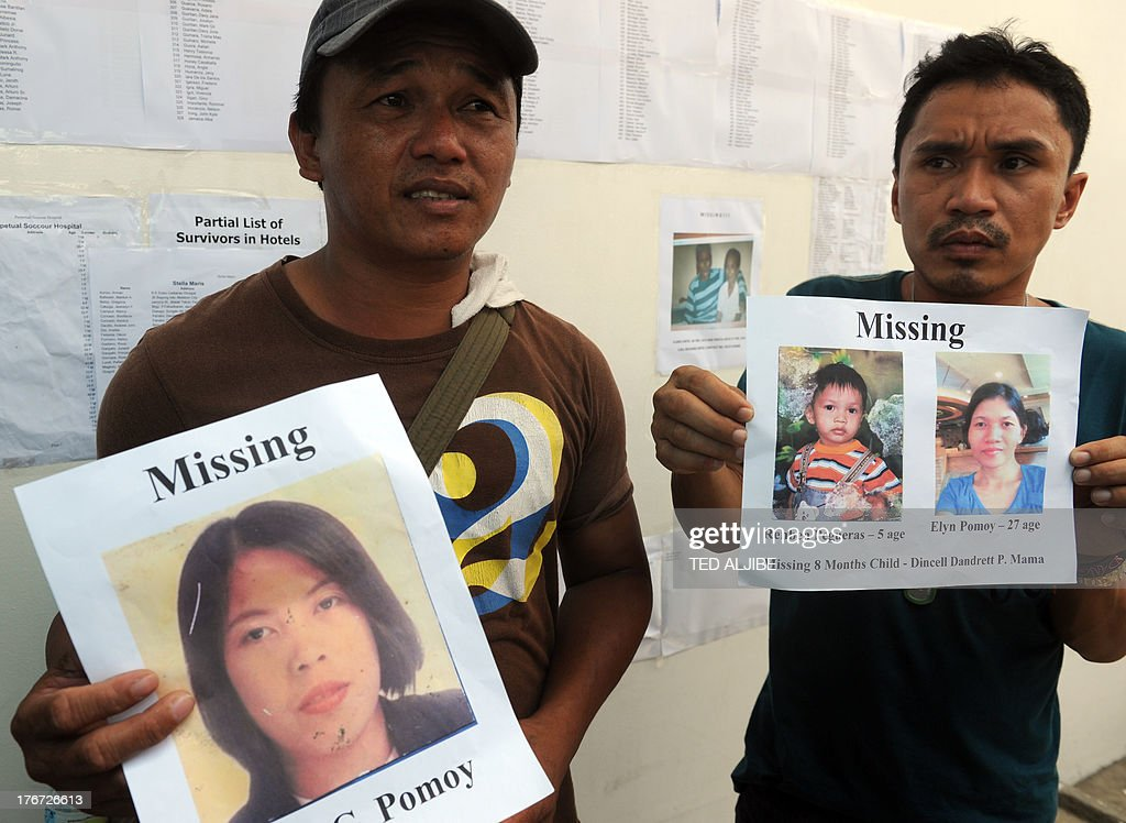 Two men show photos of their missing family who were passengers of a sunken ferry, at the company's office in Cebu City, central Philippines on August 18, 2013. Philippine rescuers struggled in rough seas August 18, as they resumed a bleak search for 85 people missing in the country's latest ferry disaster, but insisted miracle survivor stories were possible.