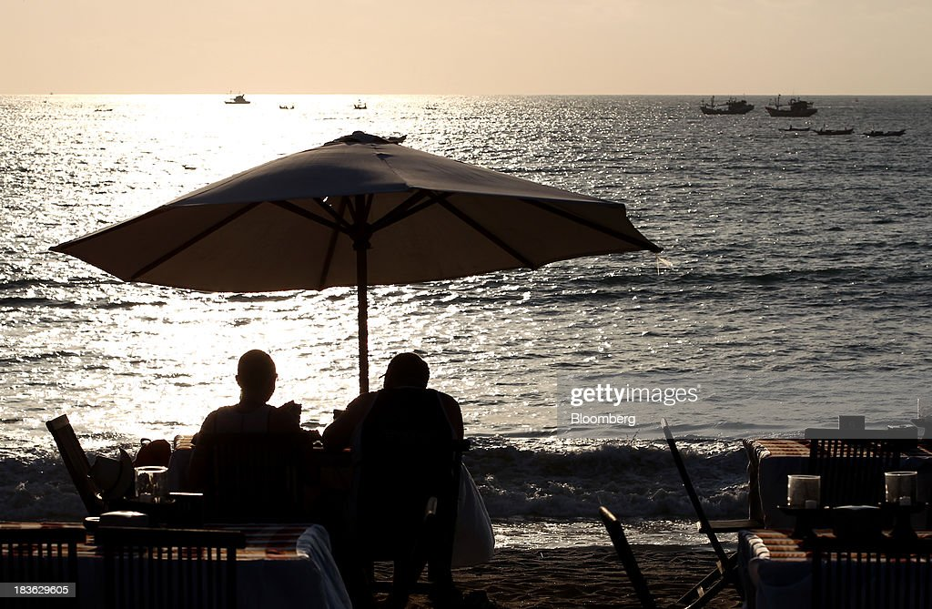 Two men sit at a beachside restaurant as the sun sets in Jimbaran, Bali, Indonesia, on Saturday, Oct. 5, 2013. Indonesia's central bank kept its key interest rate unchanged after its most aggressive tightening cycle in almost eight years as inflation pressure eased. Photographer: SeongJoon Cho/Bloomberg via Getty Images