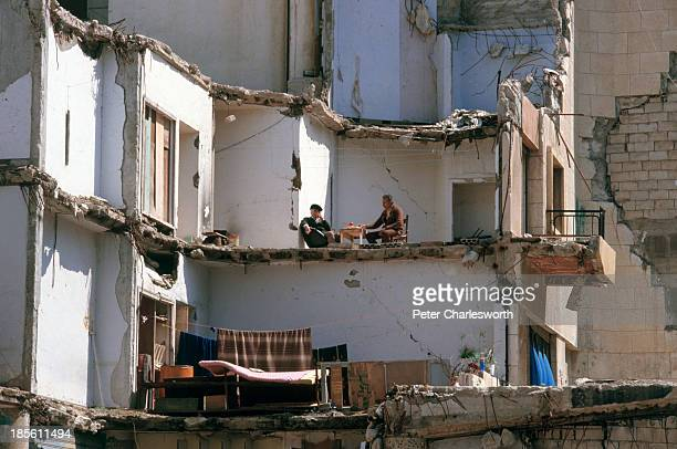 Two men sit at a table unwittingly al fresco in what remains of their devastated apartment during a lull in fighting the facade of the building have...
