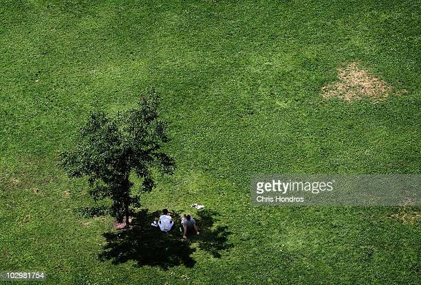 Two men sit in the shade of a tree around midday in Brooklyn Bridge Park on a hot summer afternoon July 19 2010 in the Brooklyn borough of New York...
