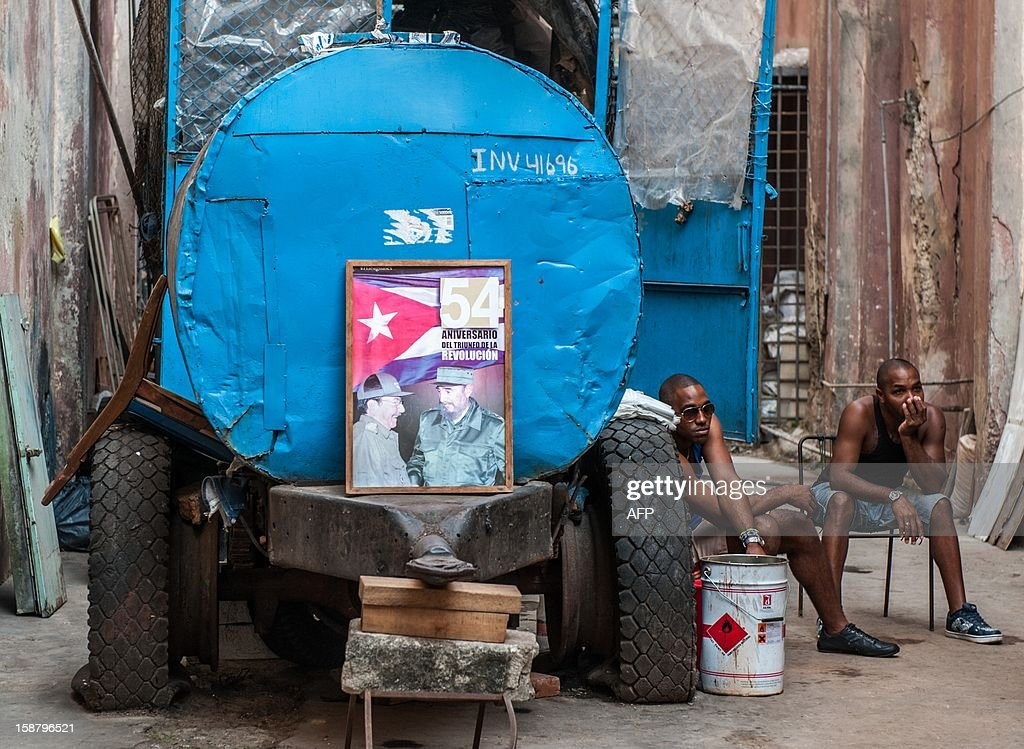 Two men sit near a poster commemorating the 54th anniversary of the Cuban Revolution in Havana on December 29, 2012.