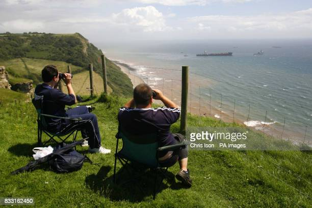 Two men sit on the cliff top waiting to see explosive devices blow apart the deck of the stricken container ship MSC Napoli off the South Devon coast...