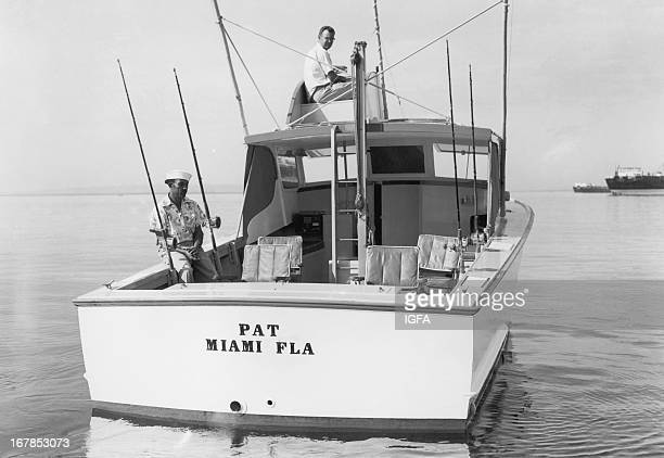 Two men sit on the fishing boat Pat based in Miami Florida as it travels the waters of Port Antonio Jamaica circa 1940
