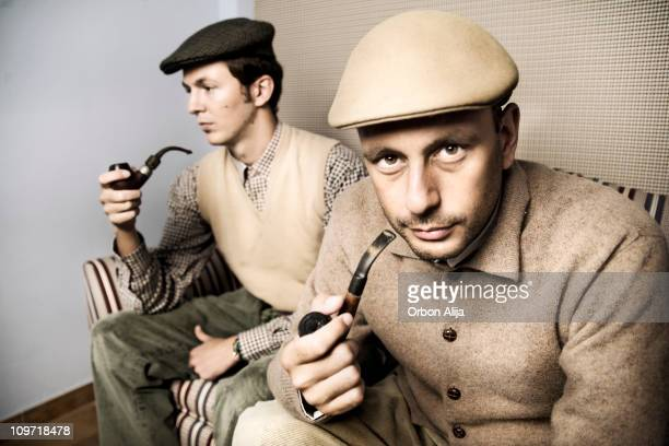 Two Men Siting on Couch Smoking Pipes