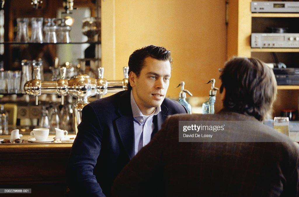 Two men sitting at bar, talking : Stock Photo