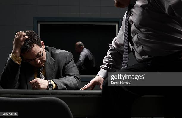 Two men sitting at desk in interrogation room