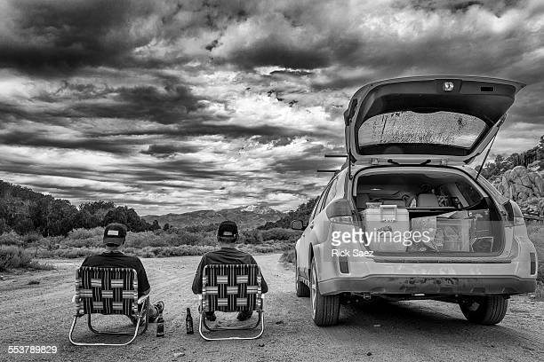 Two men sitting next to a Subaru Outback in black and white