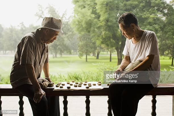 Two men sitting outdoors playing board game