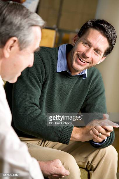 Two Men Sitting With One Another Having A Fun Discussion