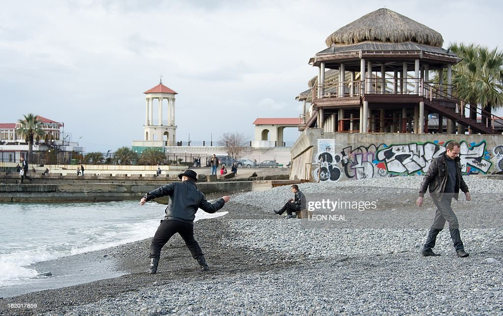 Two men skim stones in the surf on the waterfront in central Sochi, Russia, on February 18, 2013. With a year to go until the Sochi 2014 Winter Games, construction work and development continues as Olympic tests events and World Championship competitions are underway.
