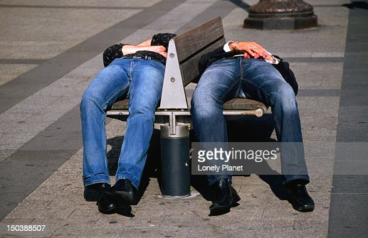 Two men sleeping on bench on Champs-Elysees. : Stock Photo