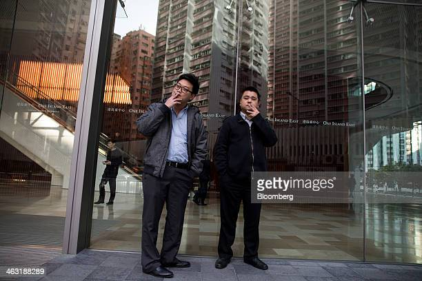 Two men smoke cigarettes outside the One Island East building at Taikoo Place operated by Swire Properties Ltd in the Quarry Bay district of Hong...