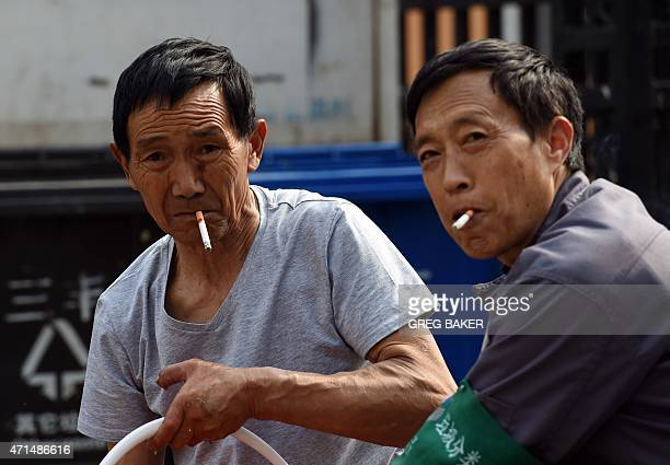Two men smoke cigarettes while clearing a drain in Beijing on April 29 2015 China has more than 300 million smokers who consume more than a third of...