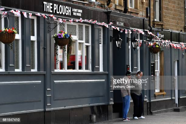 Two men smoke outside The Plough public house in Rotherham ahead of a visit from Labour Party leader Jeremy Corbyn later today on May 10 2017 in...