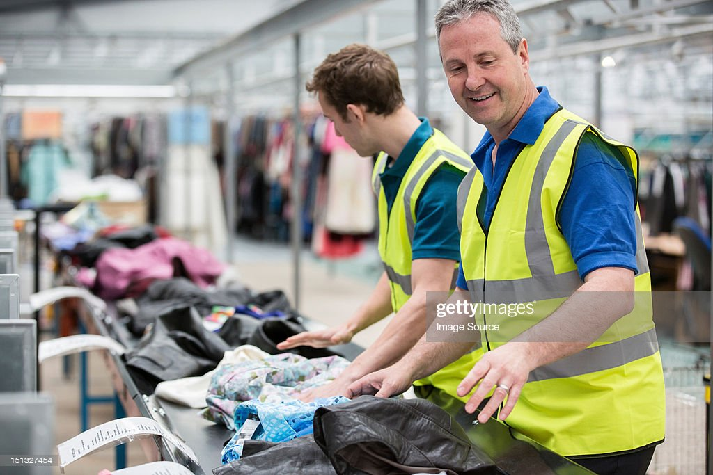 Two men sorting clothes on conveyor belt in warehouse : Stock Photo