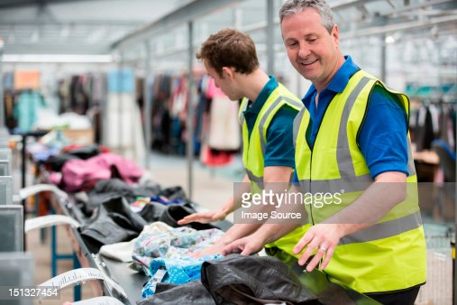Two men sorting clothes on conveyor belt in warehouse